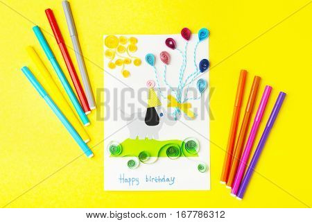 Handmade gift card and colorful felt tip pens on yellow background