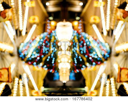 Defocused merry go round carousel detail with beautiful bokeh and silhouettes of visitors