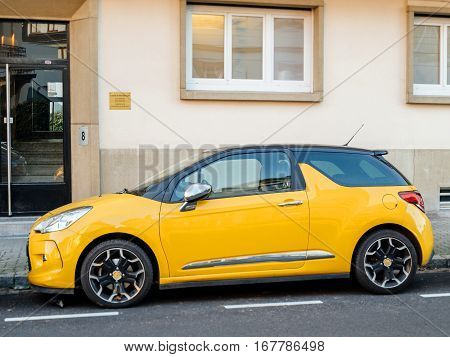 PARIS FRANCE - DEC 1 2016: Beautiful yellow Citroen sport two-doors French car parked in front of a house - tilt-shift lens