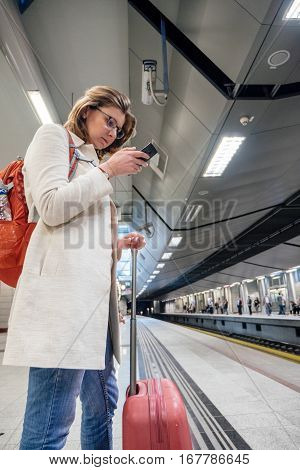 Elegant traveler woman in white coat waiting for train and surfing the mobile internet on a smartphone in the Athens subway train station with travel luggage bag
