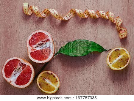 Fresh sliced Sicilian Blood orange fruits and grapefruit and centimeter ribbon on wood background, diet concept