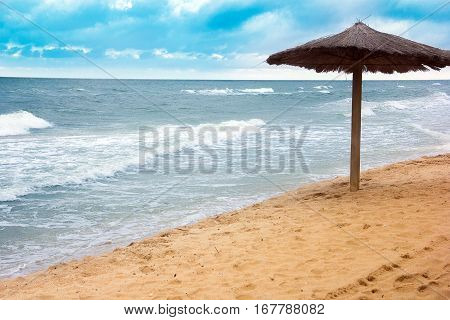 sea coast with thatched umbrella and blue sky