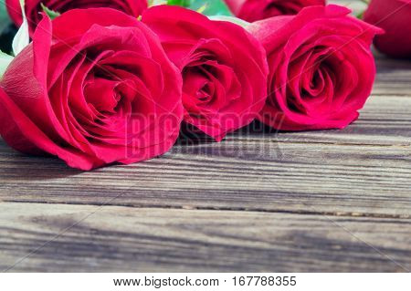 red three roses on a wooden brown background