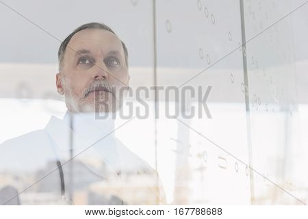 Serious senior general practitioner is thinking about his patient. He is standing and looking forward pensively. Focus on his reflection on glass wall