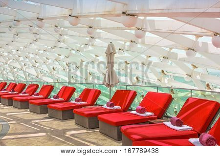 Abu Dhabi, UAE - April 22, 2013: red sun loungers in 5-star Resort Hotel Yas Viceroy in Yas Island, built over Yas Marina Circuit of Formula 1. Relax, lifestyle adult and luxury holidays concept