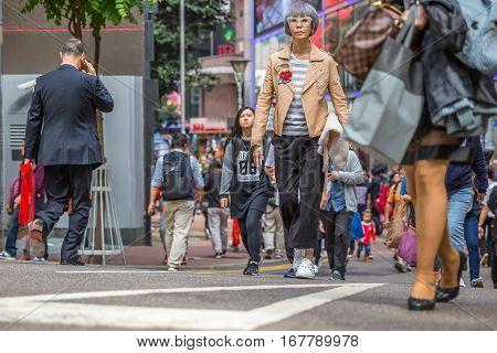Hong Kong, China - December 6, 2016: modern elegant fashion women walking in street market Jardine's Crescent, Causeway Bay, popular shopping district, full of roadside bazaar shops. low angle view.