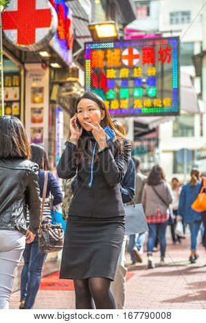 Hong Kong, China - December 6, 2016: asian busy woman walking talking at her mobile phone in Jardine's Crescent street market of Causeway Bay, on background street shops with bright shining signboards