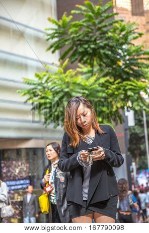 Hong Kong, China - December 6, 2016: asian woman checking her mobile phones on the street market Jardine's Crescent, Causeway Bay, famous shopping district.