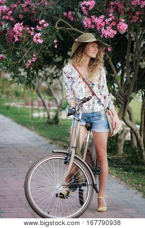 Blonde girl wearing hat and shorts with vintage bicycle and pink oleander tree behind her in park. Happy girl on vacation in resort town.