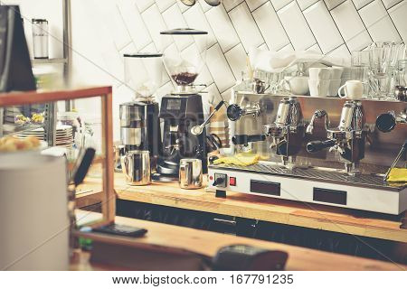 Various coffee machines, different plates, cups and glasses on cupboard in reasonably priced cafe