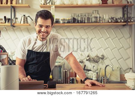 It is your bill. Cheerful barista standing at bar counter near slot machine in coffee shop. His collegue making cup of tea behind him