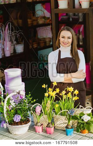 Positive florist looking at camera and smiling while standing in a flower shop.