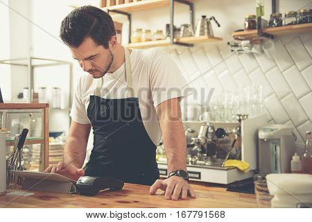 Wait a minute, please. Waist up portrait of young calm cashier making out cheque while leaning on workplace of bar counter. Different appliences are around him