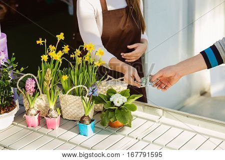 buyer giving money for payment flowers to saleswoman. Cash payment for purchase in the flower shop.