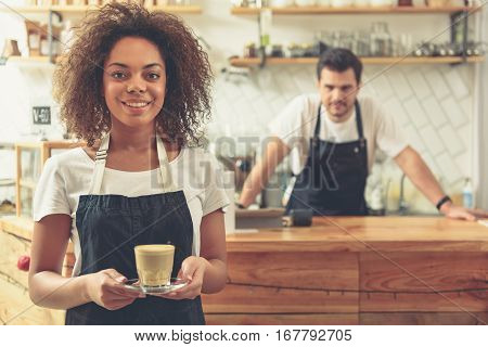 Outgoing woman keeping glass of appetizing coffee. Kind man standing behind bar counter and waiting clients