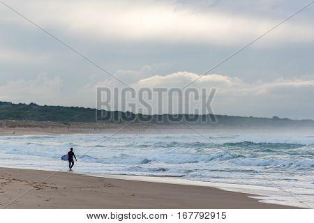 Surfer Walking Along Empty Beach