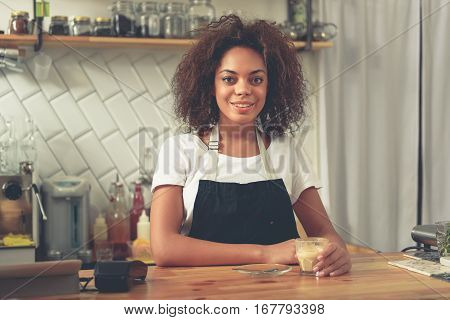 Pretty smiling woman keeping glass of warm coffee while standing at bar counter in cosy cafeteria. She drinking beverage during her break while leaning at counter