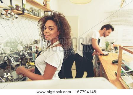 Attractive friendly woman making cup of latte with coffee machine. Unconcerned man wiping wooden stand with cash desk on it
