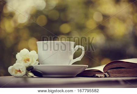Old open book and a white cup with a wild roses on a table.