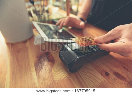 Man using close up plastic card for paying on digital tablet with access point