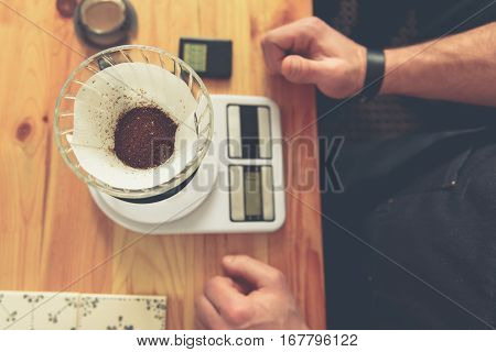 Top view close up of crumbly dried tea for making appetizing beverage in cup are on weigh-scales