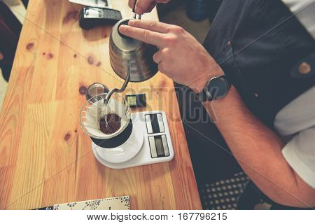 Barista brewing up tea in special cup on electrical scales for client in coffee shop