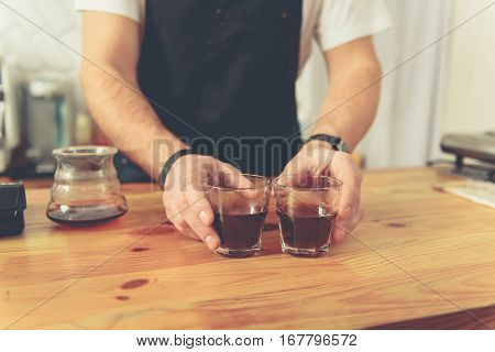 Counterman stretching out two glasses of hot flavored tea to visitor of cafeteria