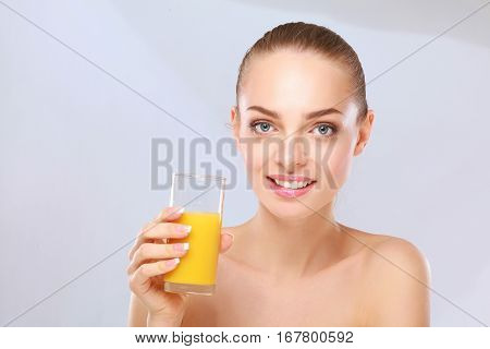 Cheerful smiling girl with towel holding a glass of orange juice.