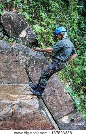 Beaufort,Sabah,Malaysia-Jan 28,2017:A man rapels with a rope over a waterfall in Beaufort,Sabah,Borneo.Waterfall Abseiling activity adventure getting famous in Sabah,Malaysia.