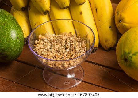Banana Papaya Avocado and Granola over a wooden table