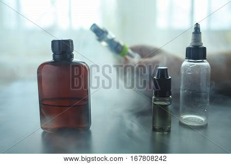 The Bottle Of Flavor For Personal Vaporiser And Other Bottles Stand On A Black Wooden Table. A Lot O