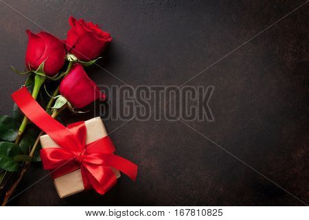 Valentines day greeting card. Red roses and gift box on stone table. Top view with space for your greetings