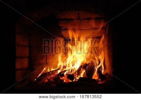 Wooden logs burning in the brick fireplace