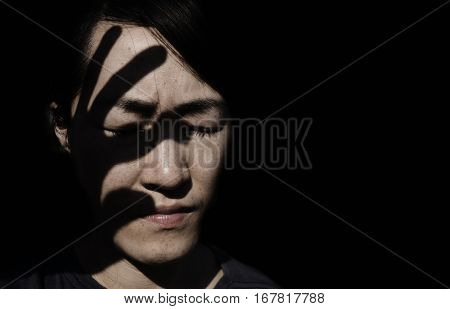 shadow of hand on woman's face(abuse concept)