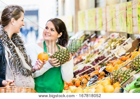 Woman buying groceries at farmers market stand. saleswoman helping her choose