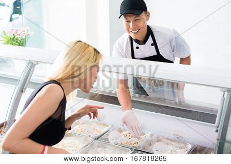 Friendly smiling deli worker helping a customer as she stands in front of a glass counter selecting food from trays