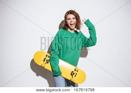 Image of happy skater lady dressed in green sweater standing isolated over white background with skateboard.
