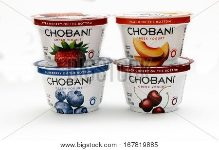 New York January 23 2017: Four containers of Chobani greek yogurt of different flavors stand against white background.