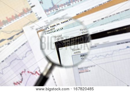 MONTREAL CANADA - JANUARY 20 2017 : Alphabet Google stock exchange ticker under magnifying glass on candlestick background.