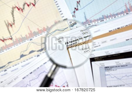 MONTREAL CANADA - JANUARY 20 2017 : Facebook stock exchange ticker under magnifying glass on candlestick background.