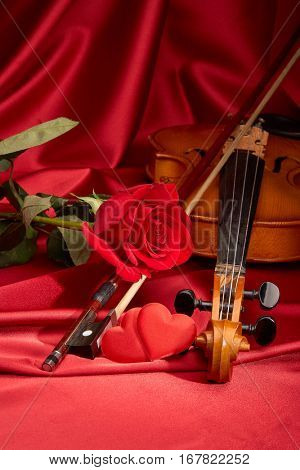Violin (fiddle), red hearts and red rose lying on the perfect red satin fabric. String instrument. Valentine's day.