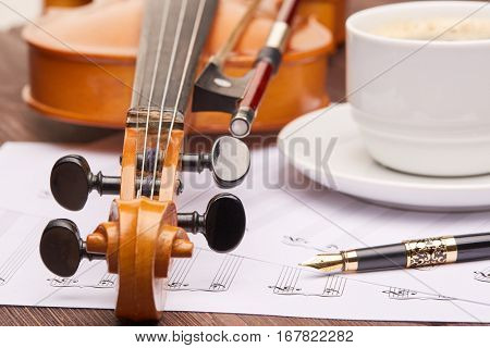 Violin, blank of paper sheet for note,  fountain pen and cup of coffee on a wooden background.