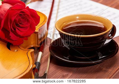 Violin (fiddle), red rose, sheet of music and cup of coffee on a wooden background. String instrument.