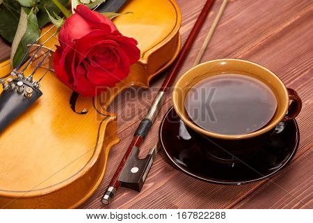 Violin (fiddle), red rose and cup of coffee on a wooden background. String instrument.