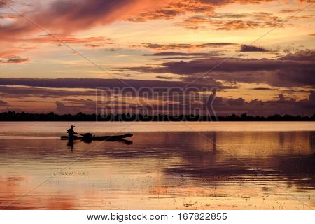 silhouette fisherman row the boat with colorful sunrise in Thailand