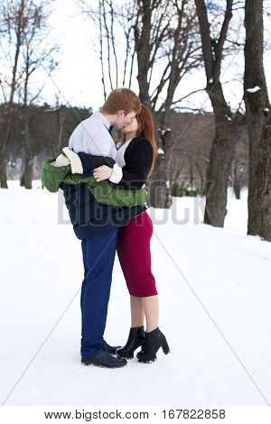 Young beautiful red-haired couple posing on a background of a winter park