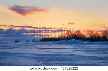 Beautiful winter landscape with sunset fiery sky and frozen lake.
