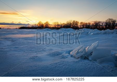 Beautiful winter landscape with sunset fiery sky and frozen lake near the shore. Composition of nature.