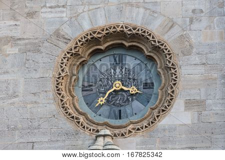 The clock with sculptures on facade of building seen from Milan Duomo's rooftop. The Milan Cathedral is the second largest church in Italy and the third in the world. poster