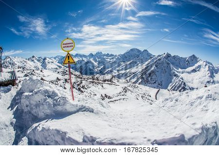 Warning sign of avalanche danger. Beautiful winter landscape with snow-covered mountains. Ski resort Elbrus. Caucasus, Russian Federation.